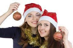 两个少妇照片圣诞节帽子的 免版税库存照片