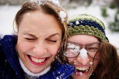 两个少妇的面孔关闭与雪 免版税库存照片