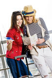 两个少妇站立带着手提箱在火车站或机场 看卡片和护照 免版税图库摄影