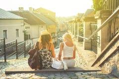 两个少妇背面图有城市地图的寻找attracti 图库摄影