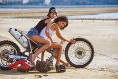 两个少妇获得使用在一辆被拆卸的摩托车的乐趣 库存图片