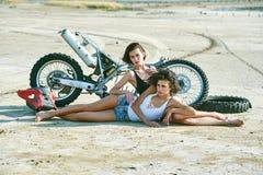 两个少妇获得使用在一辆被拆卸的摩托车的乐趣 免版税图库摄影