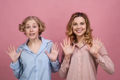 两个少妇,学生愉快地微笑并且显示在他们前面的开放棕榈表达喜悦和粗心大意 免版税库存图片
