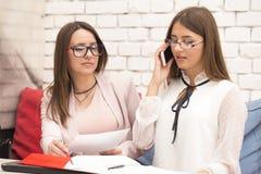 两个少妇,经理,研究一个新的项目 免版税库存图片