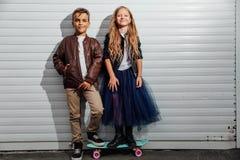 两个少年小学生画象车库门背景的在城市公园街道 图库摄影
