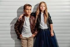 两个少年小学生画象车库门背景的在城市公园街道 免版税图库摄影