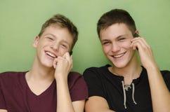 两个少年兄弟谈话在巧妙的电话 库存照片