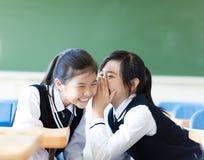 两个少年女孩说闲话在教室 库存图片