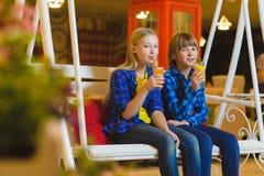 两个少年或愉快的孩子-在咖啡馆的男孩和女孩饮用的汁液 免版税库存照片