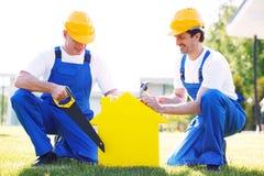 两个工作员和房子标志 免版税库存照片
