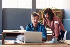 两个工友一起谈话在一台膝上型计算机在办公室 库存照片