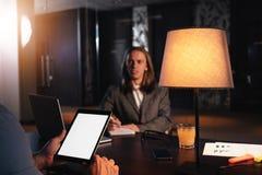 两个工友在夜顶楼办公室见面 经理举办采访 商人对话关于新的起动的 图库摄影