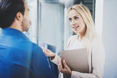 两个工友谈论企业项目在现代办公室 成功的确信的西班牙商人谈话与妇女 免版税库存图片