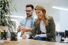 两个工友谈论经营战略在现代办公室 免版税图库摄影