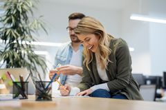 两个工友谈论经营战略在现代办公室 免版税库存图片
