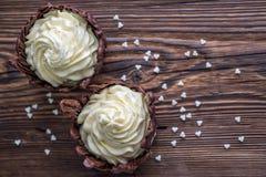 两个巧克力点心用在木桌,与白色心脏的点心上的白色奶油填装了为情人节 库存照片