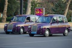 两个巴库出租汽车`伦敦等候乘客,巴库的紫色颜色出租汽车TX4 ` 图库摄影