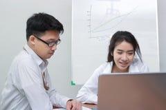 两个年轻亚裔商人一起与膝上型计算机一起使用在现代办公室 队工作企业概念 选择聚焦和sha 免版税库存图片