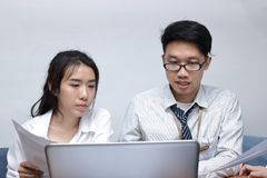 两个年轻亚裔商人一起与膝上型计算机一起使用在现代办公室 队工作企业概念 选择聚焦和sha 免版税库存照片