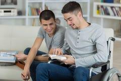 两个年轻人一本失去能力的看的书 免版税库存照片