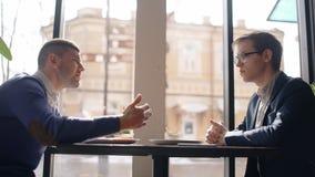两个年轻人在咖啡馆谈论起动,坐在桌上,分享想法的买卖人,谈话,有 影视素材