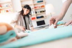 两个年轻人女商人工作在缝合的演播室 裁缝创造时装设计师衣物 免版税库存照片