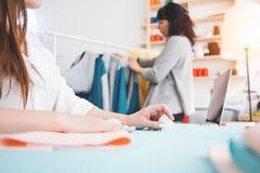 两个年轻人女商人工作在缝合的演播室 裁缝创造时装设计师衣物 免版税图库摄影