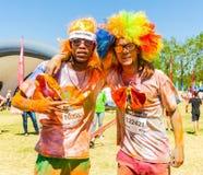 两个年轻人获得乐趣在颜色跑5km马拉松,明亮 图库摄影