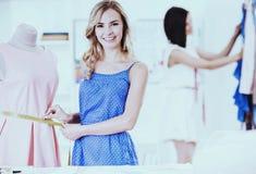 两个年轻人衣物设计师与织品一起使用在缝合的设计陈列室里 免版税图库摄影