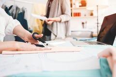 两个年轻人衣物设计师与织品和膝上型计算机一起使用在缝合的设计局 3d商业查出的小的白色 裁缝工作场所stu的 免版税库存照片