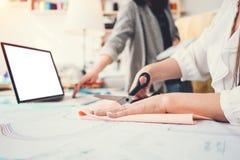 两个年轻人衣物设计师与织品和膝上型计算机一起使用在缝合的设计局 3d商业查出的小的白色 裁缝工作场所stu的 图库摄影