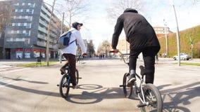两个年轻人bmx骑自行车者沿在街道的宽空的路乘坐在好日子 股票录像