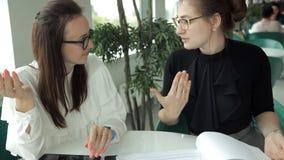 两个年轻企业女孩在咖啡馆坐并且谈论事务,要求侍者接近他们 工作,午餐 影视素材