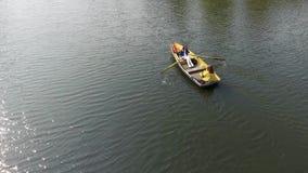 两个年轻俏丽的女孩是在小船的划船在美丽的反射性湖中间或河 一名妇女是 影视素材