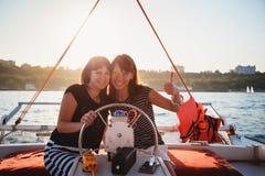 两个年轻俏丽的微笑的女孩,驾驶豪华游艇的朋友在海,显示赞许,夏天日落 库存照片