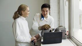 两个年轻击剑者观看的男人和的妇女操刀在便携式计算机上的讲解和分享经验在训练前 库存照片