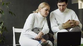 两个年轻击剑者观看的男人和的妇女操刀在便携式计算机上的讲解和分享经验在训练前 图库摄影