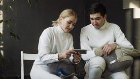 两个年轻击剑者观看的男人和的妇女操刀在智能手机的讲解和分享经验在训练以后户内 免版税库存照片