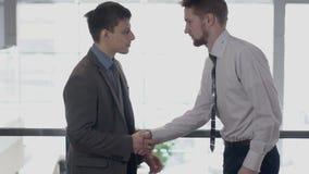 两个年轻商人是见面,握手在现代办公室 股票视频