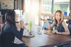 两个年轻女性朋友一起笑和吃午餐休息 免版税库存图片