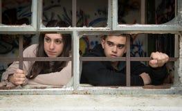 两个年轻少年,一个男孩和一个女孩,在一个残破的窗口后 库存图片