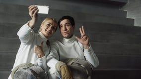 两个年轻微笑的击剑者采取在智能手机照相机的男人和妇女selfie在操刀训练以后户内 免版税库存图片