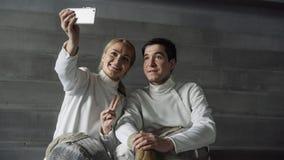 两个年轻微笑的击剑者采取在智能手机照相机的男人和妇女selfie在操刀训练以后户内 库存照片