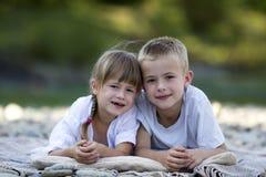 两个年轻愉快的逗人喜爱的白肤金发的放置在pebbled海滩的孩子、男孩和女孩、兄弟和姐妹在被弄脏的明亮的晴朗的夏日 免版税库存照片
