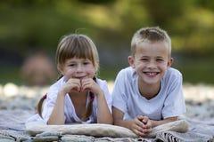两个年轻愉快的逗人喜爱的白肤金发的放置在pebbled海滩的孩子、男孩和女孩、兄弟和姐妹在被弄脏的明亮的晴朗的夏日 库存照片