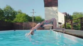 两个年轻愉快的金发碧眼的女人同步潜水入室外水池 Slowmo 股票视频