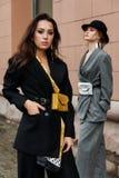 两个年轻时髦的美好的妇女时装模特儿在街道,佩带的长裤套装,帽子摆在,有在腰部的钱包 图库摄影