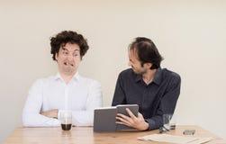 两个年轻白种人同事争论在桌上在办公室与轻的背景 库存照片