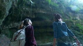 两个年轻白种人女性旅客沿一个热带洞旅行 在后面前进的背包上 启发由秀丽  股票视频