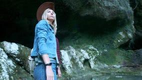 两个年轻白种人女性旅客沿一个热带洞旅行 在后面前进的背包上 启发由秀丽  股票录像